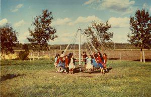 Children playing on merry-go-round, Edmonton Indian Residential School.
