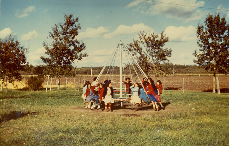 Children playing on merry-go-round, Edmonton Indian Residential School.