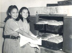 Girls baking bread, Portage la Prairie Indian Residential School.