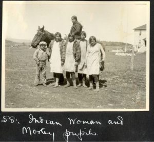 Five students of Morley Indian Residential School and a woman on horseback.