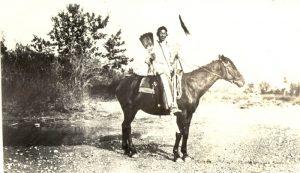 Siksika man on horseback.