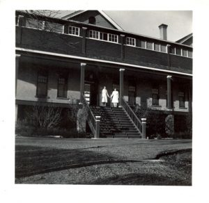 Two staff on the steps of File Hills Indian Residential School.