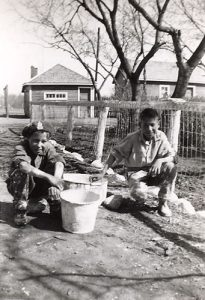 Two boys who have finished whitewashing a fence, File Hills Indian Residential School.
