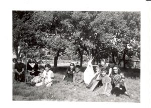 Students in theatrical costume sitting on grass.
