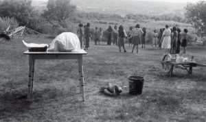 A staff member and girls at an afternoon party, with lunch waiting on the table.