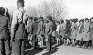 Children at flag raising that begins every school day, Round Lake Indian Residential School.