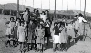 Girls with their dress-up hats on the swings.