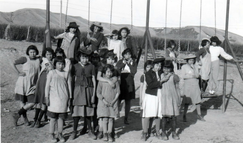 Girls with their dress-up hats on the swings of their playground.