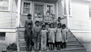 Children on the school steps with a teacher