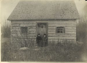 Norway House jail on Jail Island. Two government nurses sit on steps.