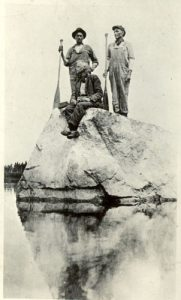 Three guides on a rock, Norway House, Manitoba.