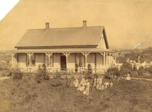 Staff on the porch and students sitting on the grass, Crosby's Girls Home, Port Simpson.