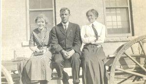Three staff sitting on a fence, Brandon Industrial Institute.