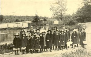 Staff and students of Crosby Girls' Home dressed in hats and overcoats, Port Simpson.