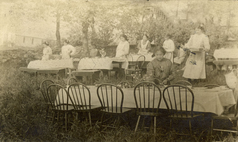 Girls setting tables for picnic.