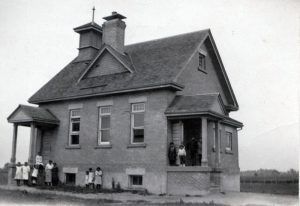 Students and staff standing outside schoolhouse, Muncey, Ontario.