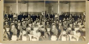Teachers and students in an assembly hall, Mount Elgin Institute. Stereograph.