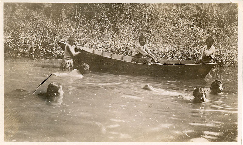 Girls in rowboat and others swimming, at Elizabeth Long Memorial Home summer camp. Kitamaat.