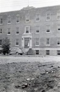 View of front of Alberni Residential School with car parked outside door.