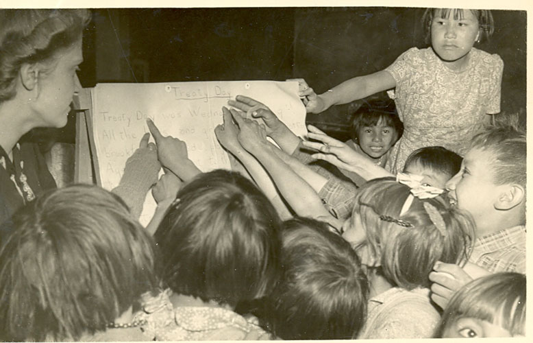 "Students pointing to the lesson ""Treaty Day,"" 1945."