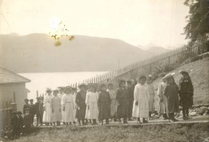 Girls and boys in hats, lined up along a boardwalk, Kitamaat.