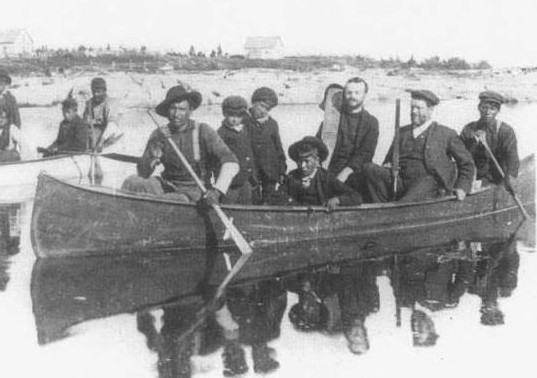 Principle Thompson Ferrier taking children to school in a canoe.