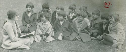 Kindergarten class with teacher sitting outside.
